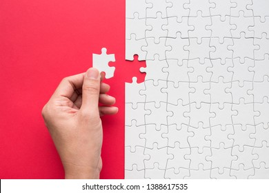 Hand putting the last piece of white jigsaw puzzle on red background and place for your content