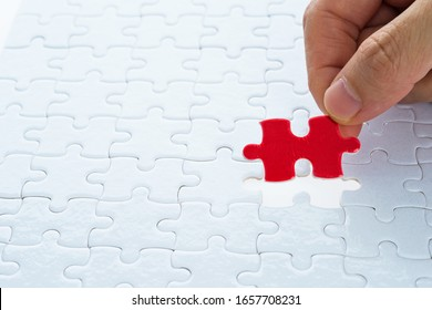Hand putting the last piece of white jigsaw puzzle.