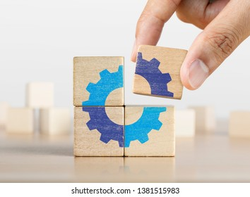 Hand putting the last piece of wooden blocks with the gear icon. Team work, unity, partnership or integration concept.