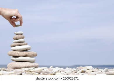 hand putting the last stone on the top of a pile of flat stones