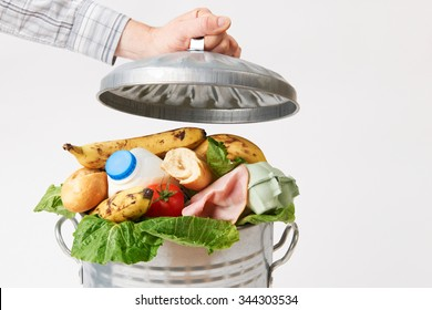 Hand Putting Lid On Garbage Can Full Of Waste Food