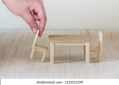 A hand putting a miniature chair to a dining table, interior design or apartment furnishing concept, invitation to have a seat at the table together