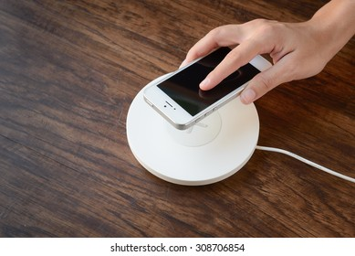 a hand putting mobile phone on a wireless charger, modern equipment, hard wood floor
