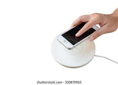 Hand putting mobile phone on wireless charger, modern equipment, isolate white background, right hand, copy space blank