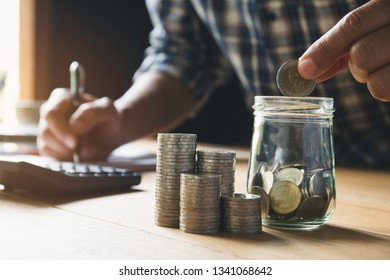 Hand putting money coin in the glass jar. Saving money, financial and accounting concept.