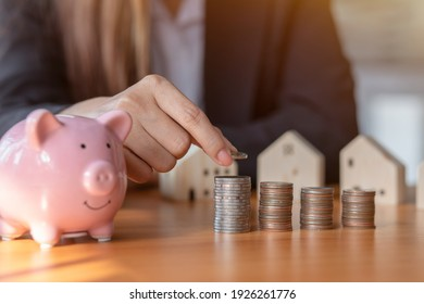 Hand putting money coin stack with wooden house,Property investment and house mortgage financial concept.