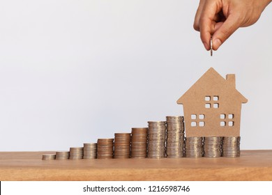 Hand putting money coins to row of coins and house model on wooden table. Concept for property ladder, mortgage and real estate investment
