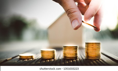 Hand putting money coins stack growing, saving money for buying house concept