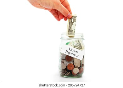 hand putting money into a down payment  jar - home buying concept