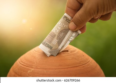 Hand putting money into piggy bank. New Indian currency of 500 rupee notes.