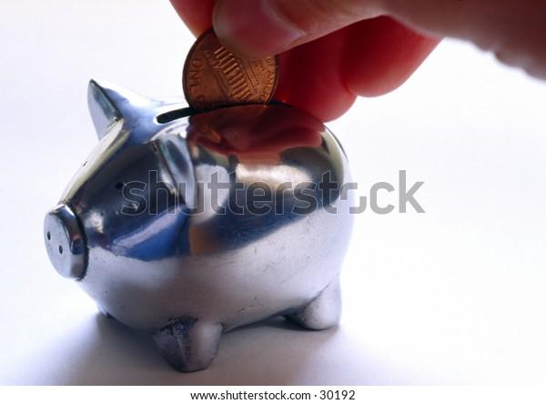 Hand putting money into a piggy bank.
