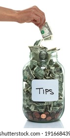 Hand putting money into a savings jar with a white tip label