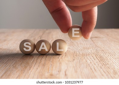 Hand putting on sale word written in wooden ball