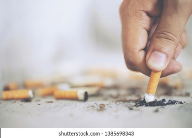 Hand putting out a cigarette,cigarette butt on Concrete floor, bare cement.