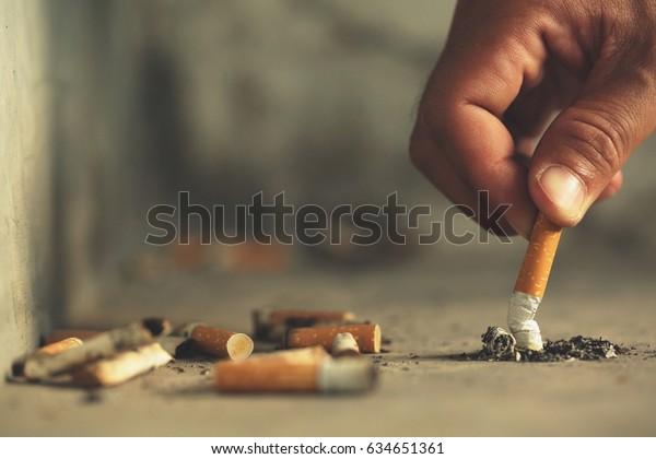 Main mettant une cigarette, mégot sur le sol en Béton, ciment nu.