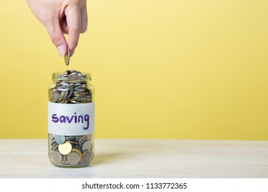 hand putting penny in a coin jar, saving money