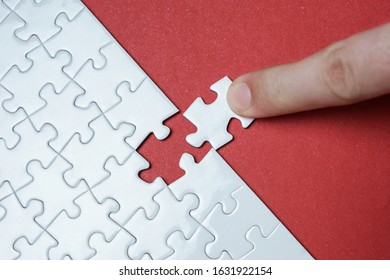 Hand putting piece of white jigsaw puzzle on red background. Team business success partnership or teamwork.