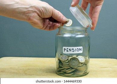 A Hand Putting A Pound Coin In To A Glass Jar. Adding Money To Your Pension Pot Concept.