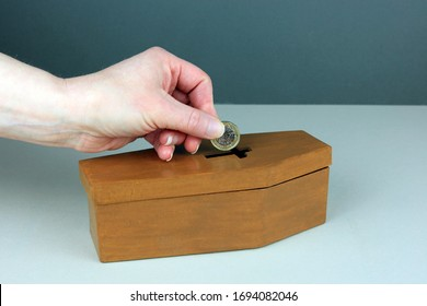 A Hand Putting A Pound Coin In To A Small Coffin Money Box. Saving For Funeral Costs Concept.