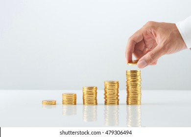 Hand putting stack of gold coins