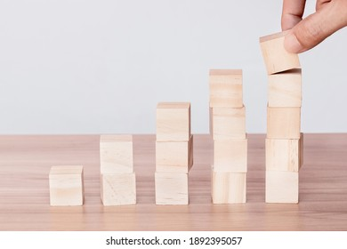 Hand putting and stacking blank wooden cubes on the table with copy space. Hand arranging wood block stacking as step stair. Business concept.