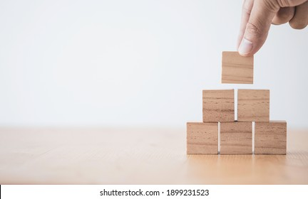 Hand putting and stacking blank wooden cubes on table with copy space for input wording and infographic icon. - Shutterstock ID 1899231523