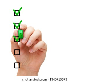 Hand putting three check marks with green marker on blank customer survey checklist on transparent glass board.