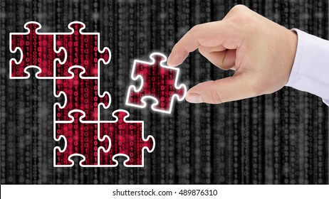 Hand putting together a puzzle uncovering red datastreams on top of a blurry grey digital matrix background data forensics and analysis concept