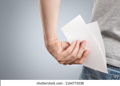 Hand putting two blank sheets of paper (tickets, flyers, invitations, coupons, banknotes, etc.) into the back pocket, isolated on grey background