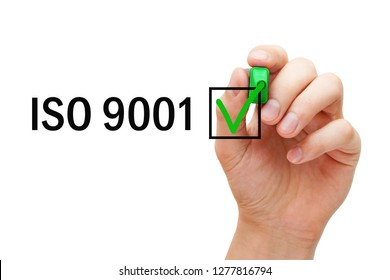 Hand putting verification check mark on ISO 9001 Quality Management System certification with green marker.