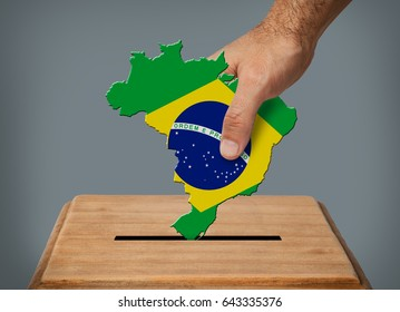 Hand putting  voting ballot with shape of Brazil into the box.