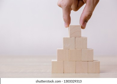 Hand putting wood cube block on top pyramid,With the concept of a thriving business going for success.