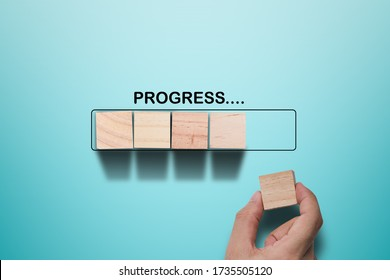 Hand putting wooden cube on virtual infographic rectangle block with progress wording. Job progressive concept.