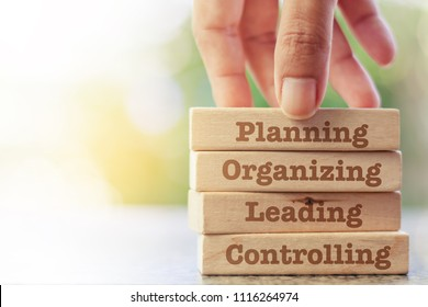 Hand putting the wooden toy with words about four functions of management: Planning, Organizing, Leading and Controlling for business and management concept