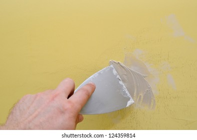 Hand with putty knife repair damaged wall