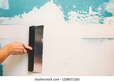 Hand with putty knife repair wall, Hand with a spatula, spatula with spackle paste structure, process of applying layer of putty trowel, working with spackling paste