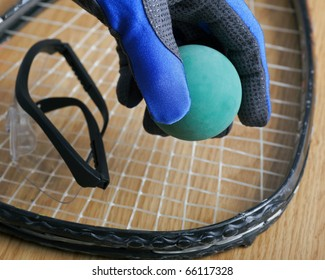 Hand in racquetball glove picking up ball.