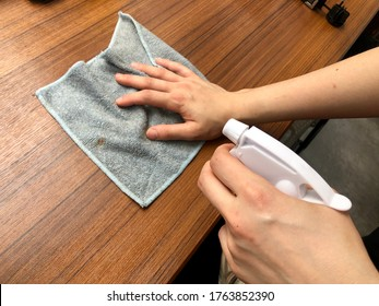 Hand with a rag and alcohol sanitizer spray to dust the wood table. Cleaning and protection from coronavirus, germ and bacteria on furniture surface. Restaurant counter seat.