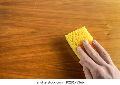 Hand with a rag wipes the table, doing cleaning
