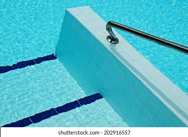 Hand rail at entrance to a swimming pool with ripples on water surface producing an abstract background.
