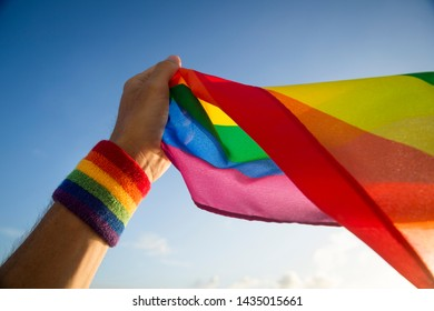 A hand with rainbow color wristband waving gay pride flag backlit in the wind against golden sunset sky