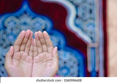 Hand raised up for dua on praying mat