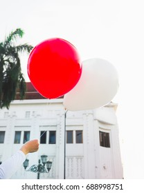 Hand raising colorful red and white balloons with Indonesian Flag theme