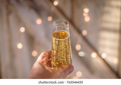 hand rasing a glass of champagne for a toast with twinkling lights in background
