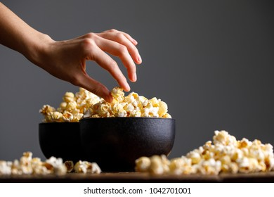The hand reaches for a bowl with tasty popcorn. Still-life on a wooden background.