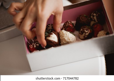 hand reaches for the gift box with strawberries in white and black chocolate and takes from there the sweetness