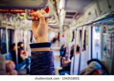 A hand reaches up to a handle on a subway train in Yokosuka, Japan.