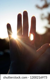 Hand reaches for the sky and covers the sun, the sun's rays make their way through the hand, close - up
