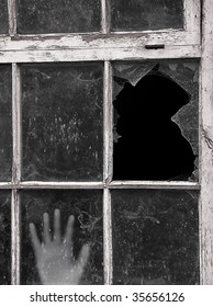 Hand reaches up to touch old dirty Window with focus on smashed pane