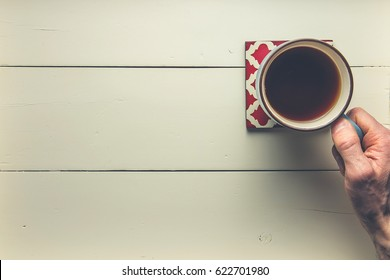 Hand reaching for coffee mug on wood